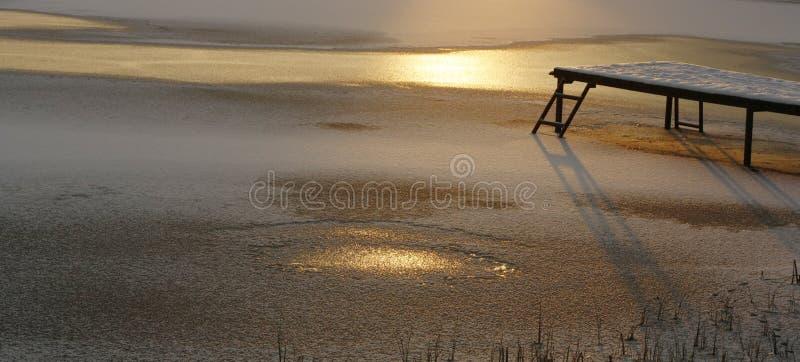 Djupfryst sjö i solstrålar och en pir på solnedgången arkivfoto