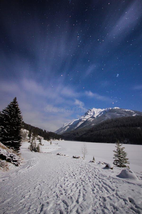 Djupfryst sjö och snöig bana i berg under kall natt under himmel mycket av stjärnor och faslty flödande moln, två Jack Lake, Banf arkivbilder