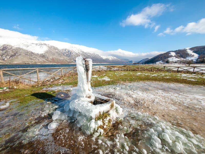 Djupfryst springbrunn på berglandskap med det snöade locket arkivbild