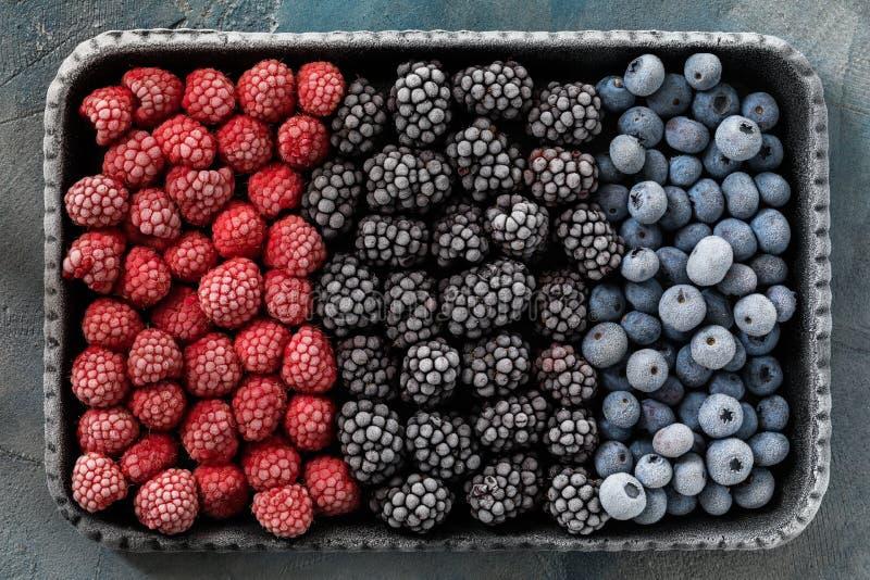 Djupfrysta bär av hallon och blåbär i ett magasin royaltyfri bild
