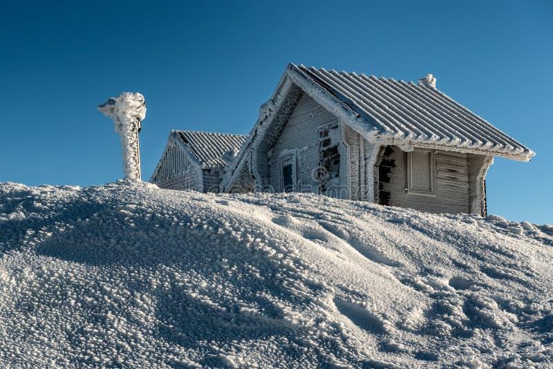 Djupfrysta bergstugor och snöig vinter royaltyfria bilder
