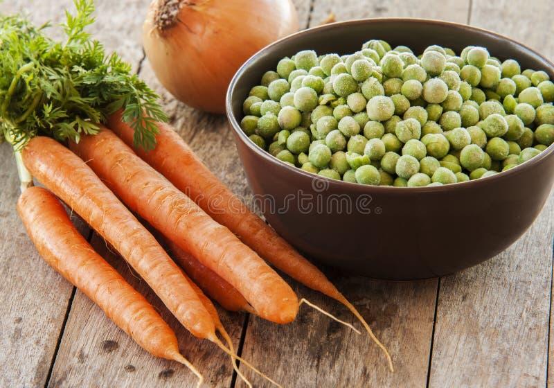 Djupfrysta gröna ärtor med morötter royaltyfri bild
