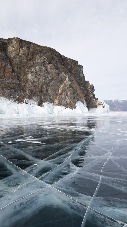 Djupfrysta Lake Baikal i Ryssland Härligt vagga, ljusa stora sprickor på yttersidan av sjön och iskvarteren nära kusten fotografering för bildbyråer
