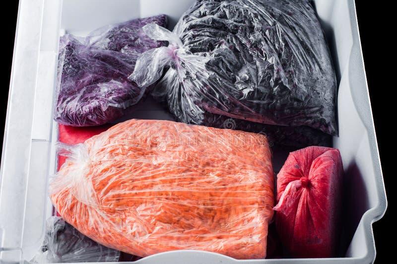Djupfrysta mosade jordgubbar, morötter, vinbär i en plastpåse i en enhet från kylskåpsvartbakgrunden, isolat arkivbild