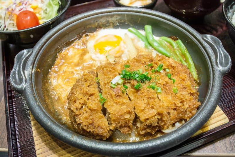 Djupt avfyrat griskött kokade med den nya äggöverkanten på risbunken royaltyfri bild