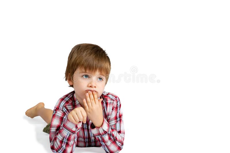 Djupt i tanke lägger pojken på magehanden till kanter arkivfoto