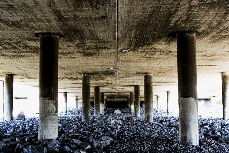 Djupt och grovt perspektiv från under en konkret bro royaltyfri bild