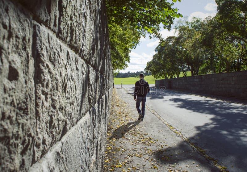 Djupt perspektiv längs en stenvägg och en man som går i en höstgata royaltyfri bild