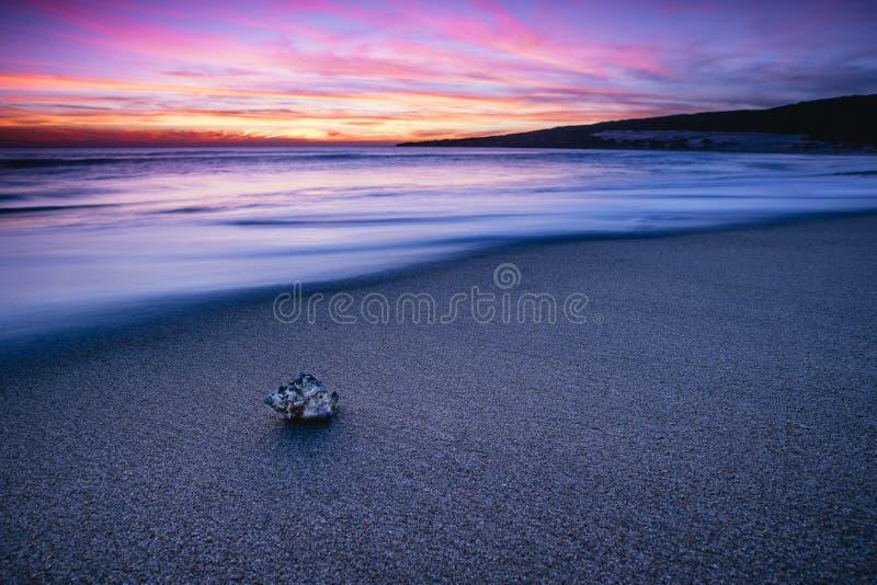 Djupt - purpurfärgad solnedgång i den Tarifa stranden, Andalusia arkivfoto