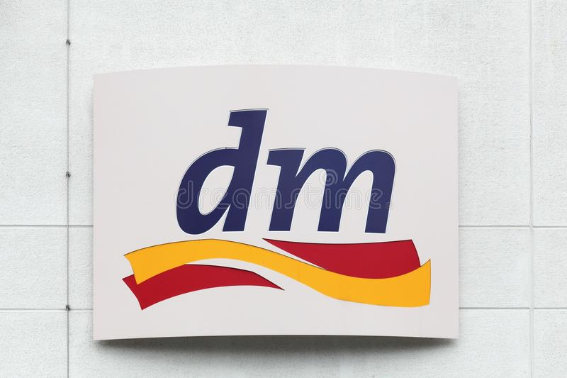 DM logo on a wall. Frechen, Germany - July 22, 2017: DM logo on a wall. dm-drogerie markt is a chain of retail stores that sells cosmetics, healthcare items stock images