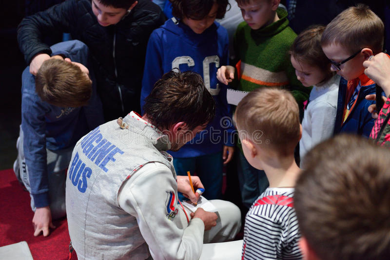 Dmitry Rigin geeft autographs aan kinderen stock fotografie