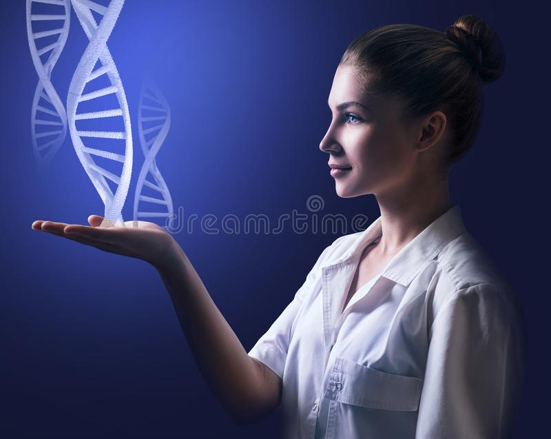 DNA chains flows from hand of young female doctor. DNA molecules flows from hand of young female doctor over dark blue background stock image