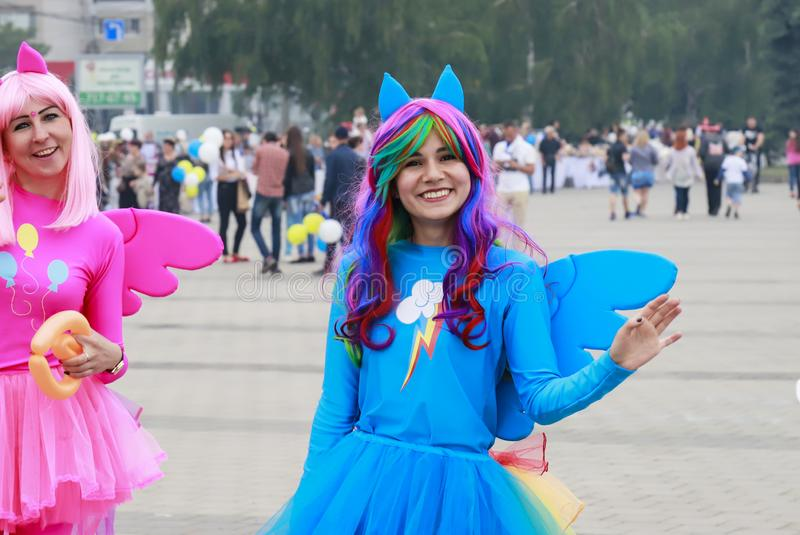 Two funny young girls  in blue and pink bright carnival dresses are smiling and walking along the street at the festival in Dnepr royalty free stock image