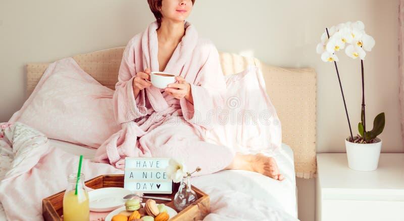 Dnia dobrego nastrój Żadny twarzy kobieta w bathrobe obsiadaniu na łóżku z kawą i śniadanie w łóżku z dalej Mieć ładnego dnia tek obrazy royalty free