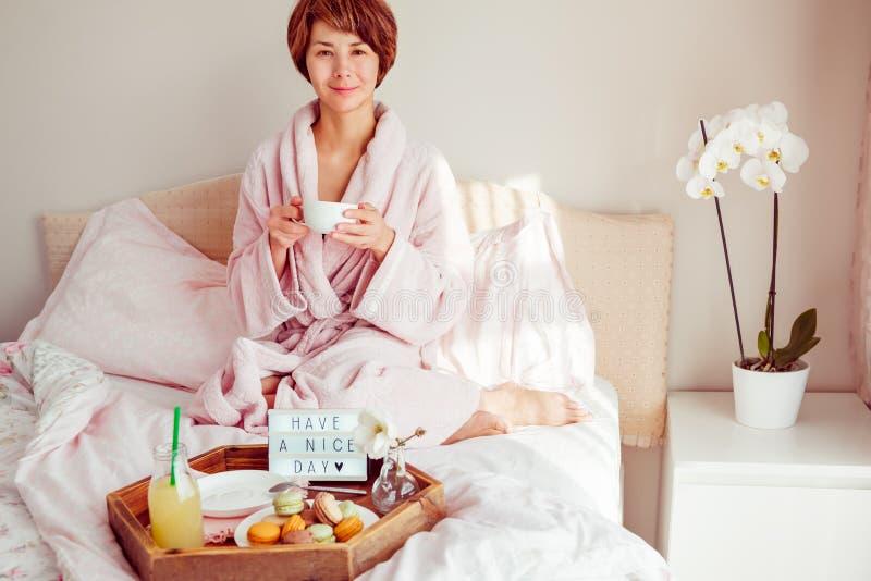 Dnia dobrego nastrój Młoda kobieta w bathrobe obsiadaniu na łóżkowym, pijący kawę i jej śniadanie w łóżku z Mieć ładnego dzień obraz royalty free