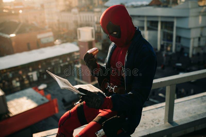 DNIPRO,乌克兰- 2019年3月28日:摆在与蛋糕和报纸的Deadpool cosplayer在他的手上 库存图片