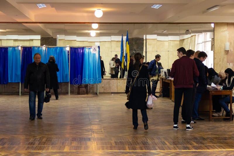 DNIPRO, УКРАИНА - 21-ое апреля 2019: Избиратели около кабины для голосования на избирательном участке во время второго круга избр стоковое изображение rf