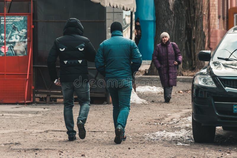 DNIPRO, УКРАИНА - 2-ое марта 2019: 2 люд идя вниз по улице Дизайн стороны бульдога на пальто назад Плакат рекламы кока-колы стоковое изображение rf