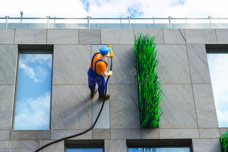31.07.2019, Dnipro city, Dnepropetrovsk, Ukraine. A sculpture of a worker in uniform watering grass stands on the wall of the royalty free stock photos