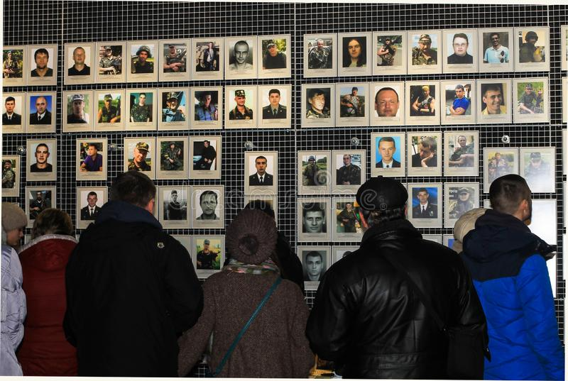 Dnipro city, Ukraine. People stand near portraits of a dead soldiers, fighters of the Ukrainian Army, in the Museum of the ATO stock photo