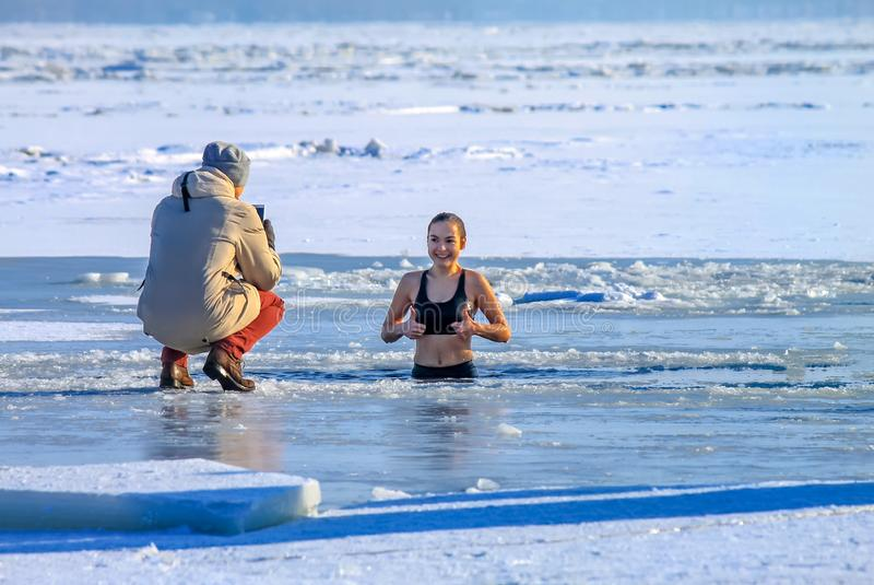 Dnipro city, Ukraine. Winter sport. Beautiful girl swims swims in the winter river covered with ice during the Orthodox royalty free stock photography