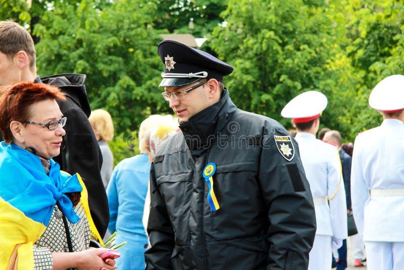 Dnipro, Dnepropetrovsk, de Oekraïne, 12 Mei, 2018, een Oekraïense politieman spreekt aan een vrouw bij een vakantie Politieagent  royalty-vrije stock afbeeldingen