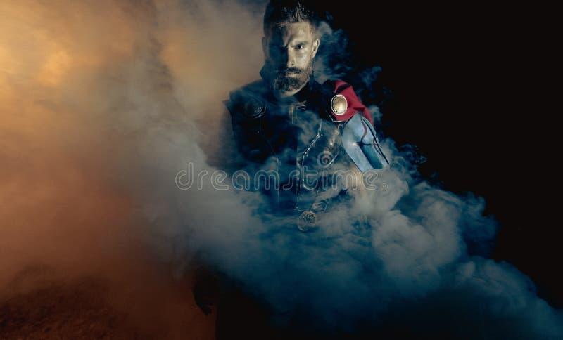 Dnipro, Ucraina 5 giugno 2019: Cosplayer illustra il supereroe Thor contro il fondo del fumo immagini stock