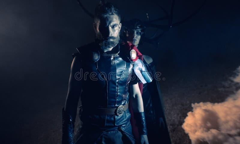 Dnipro, Ucraina 5 giugno 2019: Cosplayers ritrae il supereroe Thor e la dea Hela contro il fondo del fumo immagini stock