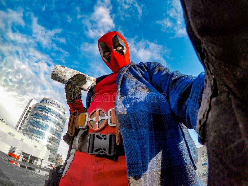DNIPRO, UCRAINA - 28 MARZO 2019: Cosplayer di Deadpool che posa contro il paesaggio ed il cielo urbani fotografia stock libera da diritti