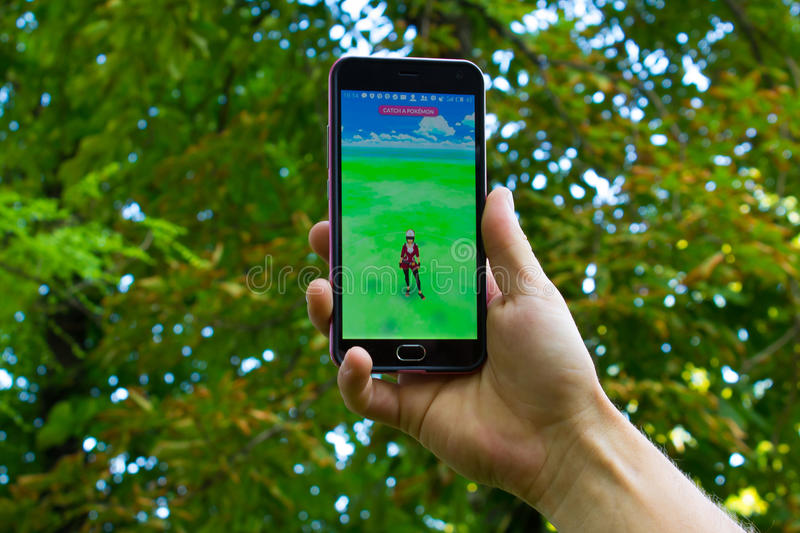 Dnipro, Ukraine - July 23, 2016: The hit augmented reality smartphone app Pokemon GO shows a encounter overlain in park stock photography