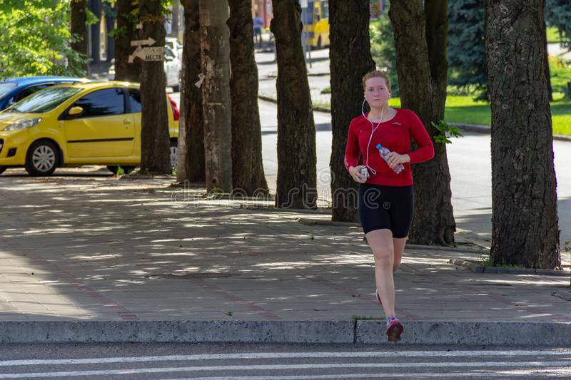 DNIPRO, UKRAINE - June 16, 2019: Young girl goes for sports on street. Wellness jogging. Woman in red T-shirt sneakers and black stock photos