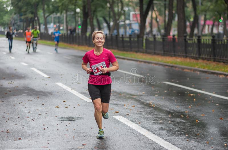 Happy female participant running on Dnipro city street during 42 km distance of ATB Dnipro Marathon. DNIPRO, UKRAINE - SEPTEMBER 16, 2018: Happy female stock photos