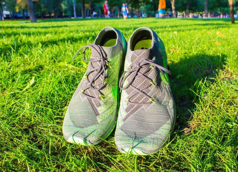 Dnipropetrovsk, Ucrania - agosto, 21 2016: Nuevos zapatos del nike del estilo en la hierba verde - editorial ilustrativo fotografía de archivo
