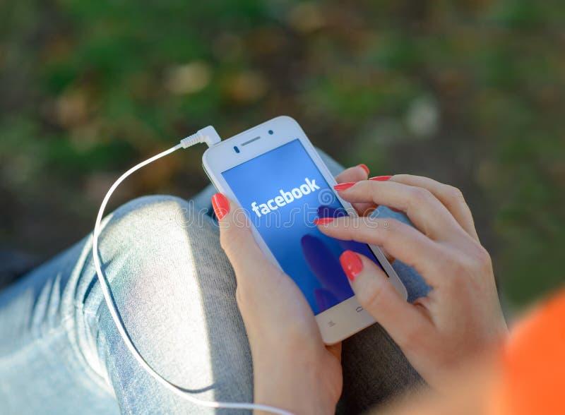 DNIPROPETROVSK UKRAINA, WRZESIEŃ, - 18, 2014: Młoda Kobieta Używa Facebook sieci Ogólnospołecznego zastosowanie na Mądrze telefon obraz stock