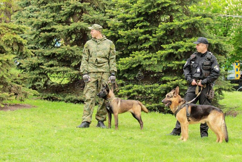 Dniprostad, Dnepropetrovsk, de Oekra?ne, 9 Mei, 2018 De Oekraïense managers van de politiehond met opgeleide herdershonden besche royalty-vrije stock afbeeldingen