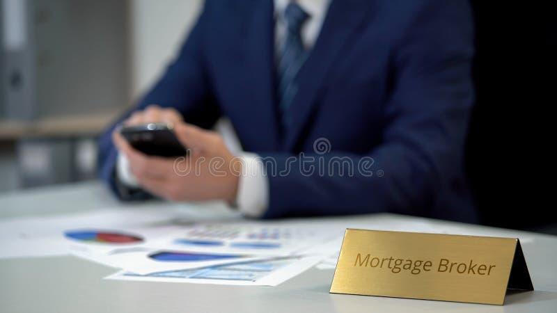 Doświadczony hipoteczny makler używa wiszącą ozdobę app, studiuje sytuację na rynku obraz stock