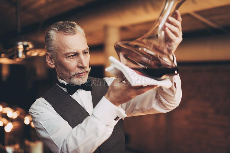 Doświadczeni eleganccy sommelier spojrzenia przy wino cedziny w dekantatorze Wina degustation zdjęcia royalty free