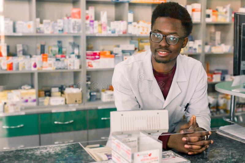 Doświadczona amerykanin afrykańskiego pochodzenia mężczyzny farmaceuta w białym żakiecie pracuje w nowożytnej aptece obraz royalty free