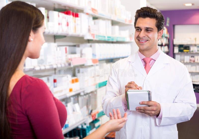 Doświadczona farmaceuta doradza żeńskiego klienta obraz stock