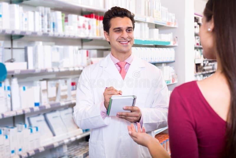 Doświadczona farmaceuta doradza żeńskiego klienta zdjęcia stock