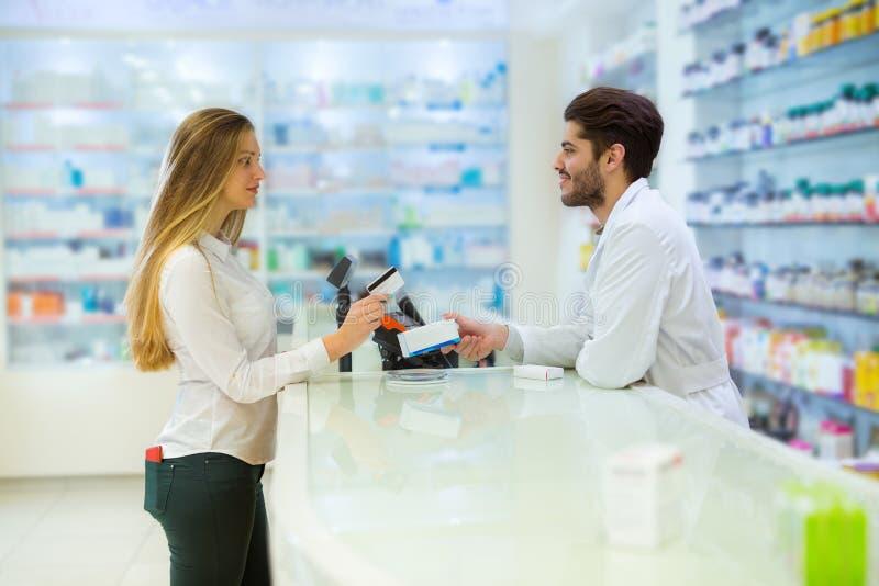 Doświadczona farmaceuta doradza żeńskiego klienta zdjęcie royalty free
