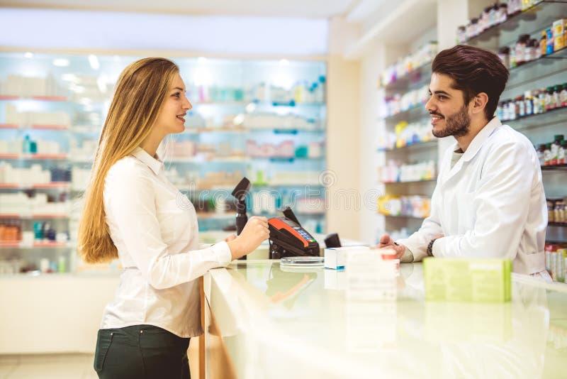 Doświadczona farmaceuta doradza żeńskiego klienta w aptece zdjęcie royalty free