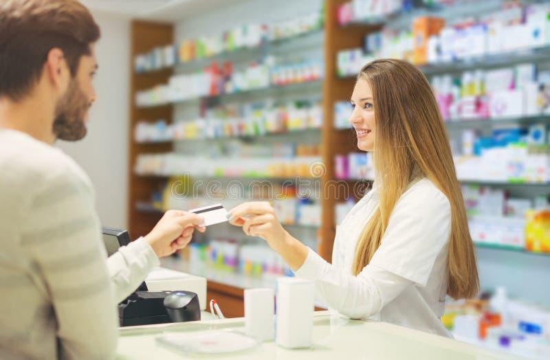 Doświadczona farmaceuta doradza męskiego klienta w aptece obrazy stock