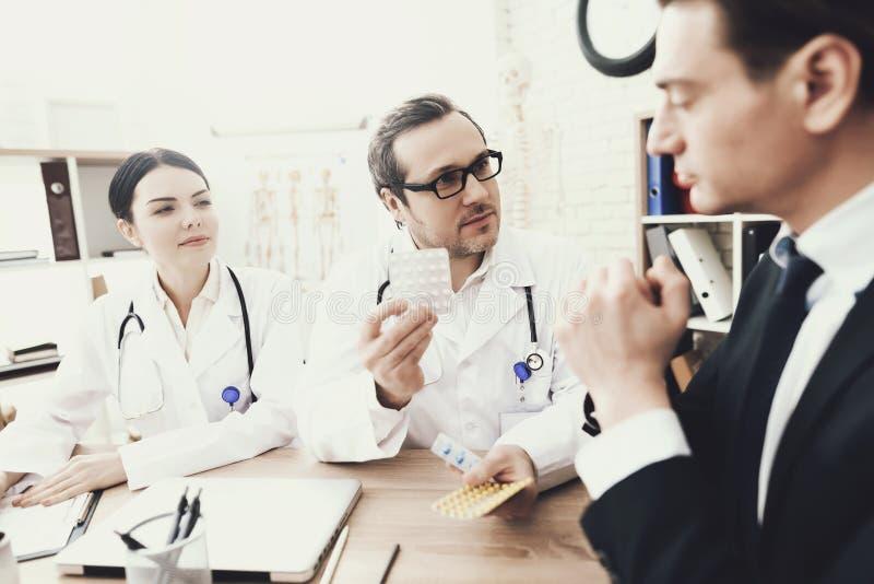 Doświadczona lekarka przepisuje pacjent o dosage pastylki przy medycznym biurem zdjęcia stock