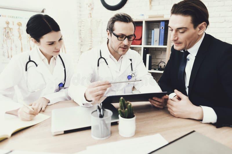 Doświadczona lekarka radzi biznesmena w medycznym biurze Konsultacja z uczęszczać lekarza zdjęcia stock