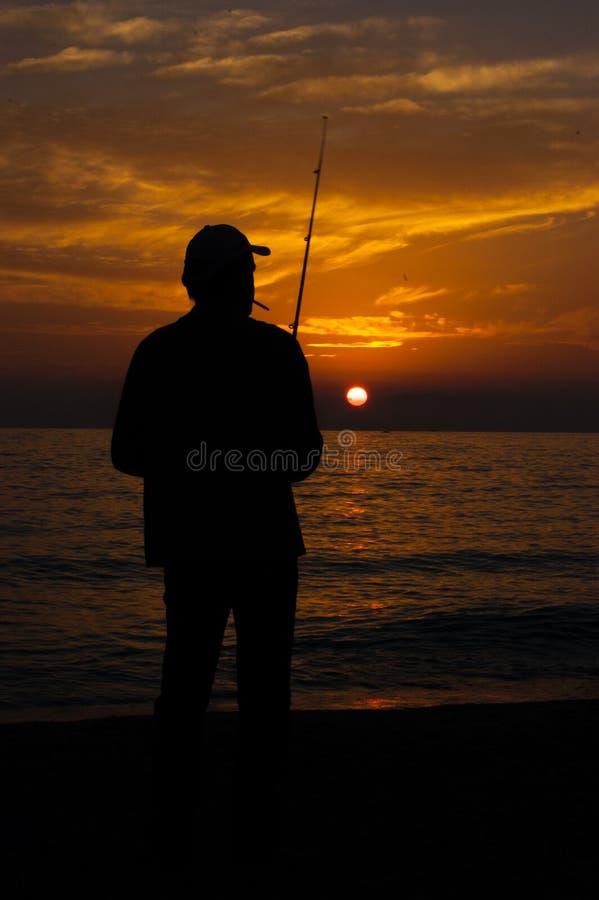 Doświadczona rybak sylwetka dymi papieros przeciw położenia słońcu fotografia royalty free