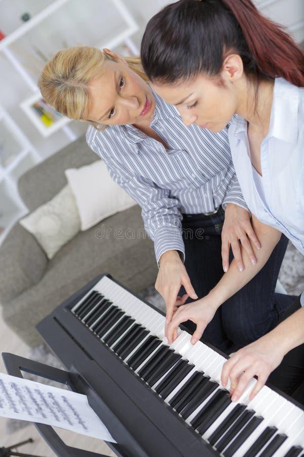 Doświadczonego kobieta mistrza fortepianowa ręka pomaga ucznia obrazy stock