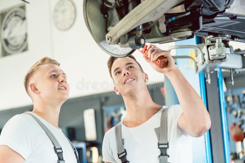 Doświadczony auto mechanik uczy aplikanta o talerzowych hamulcach zdjęcia stock