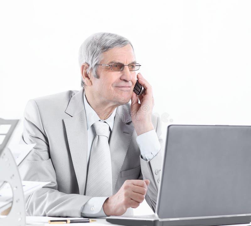 Doświadczony biznesmen z telefonu komórkowego obsiadaniem przy jego biurkiem zdjęcia royalty free