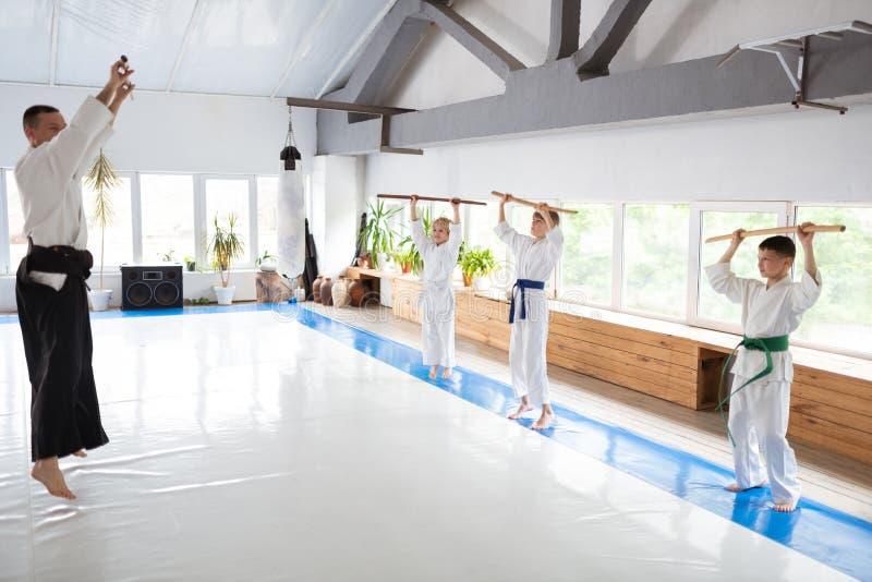 Doświadczony dojrzały nauczyciel pokazuje dzieciom aikido ruchy fotografia royalty free